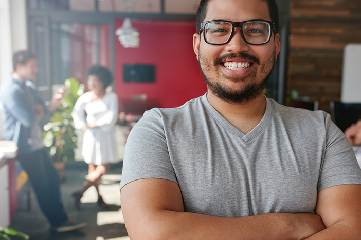 Smiling male entrepreneur looking at camera at office. Mixed race male creative professional with colleagues talking in background.