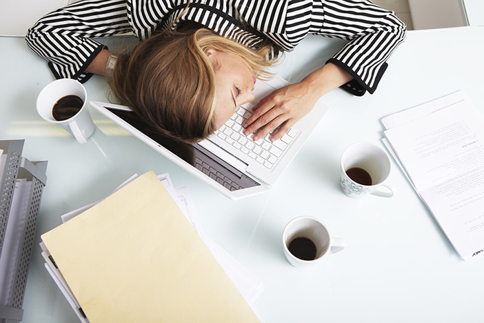 female in black striped shirt laying head on laptop three coffees, file folders, paperwork on desktop